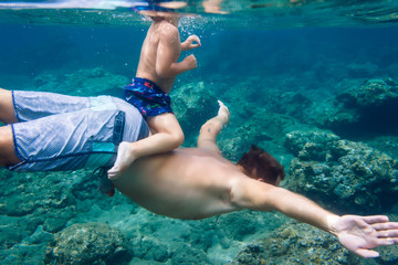 Father and son diving under water,Bali,Indonesia