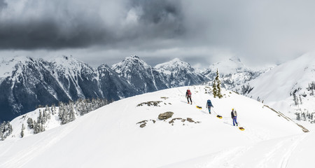Climbers dragging sleds of gear in snowy mountains