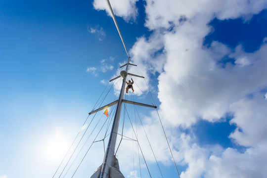Man hanging from mast of sailboat, Lombok, Indonesia