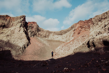 Photographer taking picture surrounded by volcanoes, Lanzarote, Canary Islands, Spain