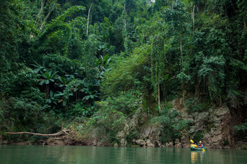 A man paddles his packraft as dense jungle towers above him on the Nam Ou River, Laos.