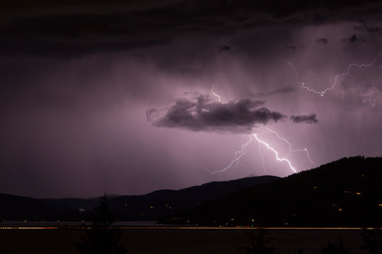 Long exposure of lightning storm in the mountains with cars blurring on bridge