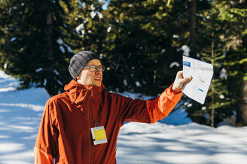 Man holding map while hiking in winter, Whistler, British Columbia, Canada