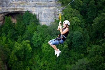 Woman riding zip line above Guam gorge, Krasnodar Krai, Russia
