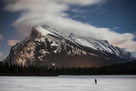 Man playing hockey on frozen lake, Canada