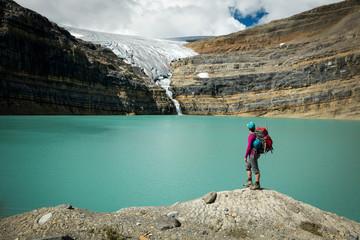 Person standing by lake in Bow Glacier, Banff, Alberta, Canada