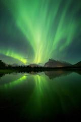 Aurora Borealis above lake and mountains in Banff National Park