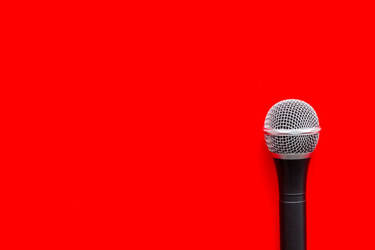 blogger, journalist or musician office desk with microphone on red background top view copyspace