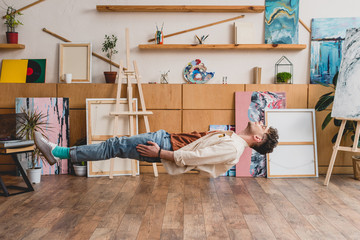 handsome artist with closed eyes levitating over wooden floor in painting studio