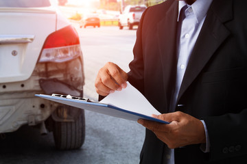 insurance officer writing on clipboard while insurance agent examining black car after accident.