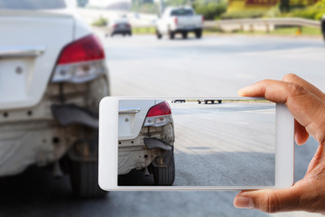 Car insurance agents take pictures of accident-damaged vehicles with a smartphone as a proof of insurance claim