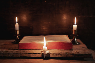 A bible open on a table next to a candle. The light illuminating the bible is only from the candle. Perfect for religion, easter and christmas themes.