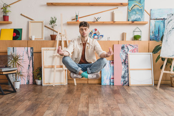 handsome artist with closed eyes levitating in lotus pose in gallery