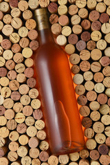 A bottle of white zinfandel surrounded by corks standing on end filling the frame
