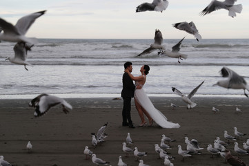 A wedding couple poses for pictures at New Brighton beach in Christchurch