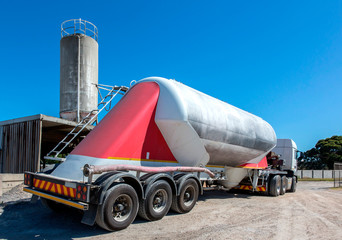 Cement delivery truck with multiple wheels and silo in background