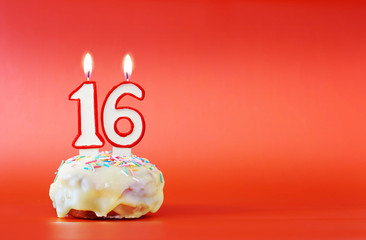 Sixteen years birthday. Cupcake with white burning candle in the form of number 16. Vivid red background with copy space