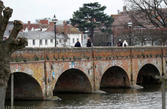 Visitors walk across the foot bridge leading to the centre of Stratford-upon-Avon