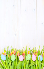 Tulips  and easter eggs on wooden background. Backdrop with empty space for text