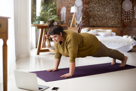 Young woman doing yoga at home while looking at laptop