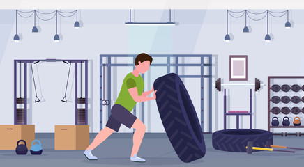 sports man flipping a tire doing hard exercises guy working out in gym crossfit training healthy lifestyle concept modern health club studio interior horizontal