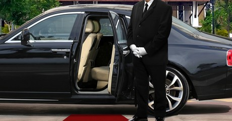Limo driver standing next to opened car door with red carpet Wall mural