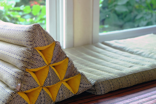 Triangle backrest pillow and folding mattress prepared closed to window exit of living room to the outside green garden