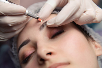 Permanent Makeup For Eyebrows. Microblading brow. Beautician Doing Eyebrow Tattooing For Female Face. Beautiful young girl in a beauty salon