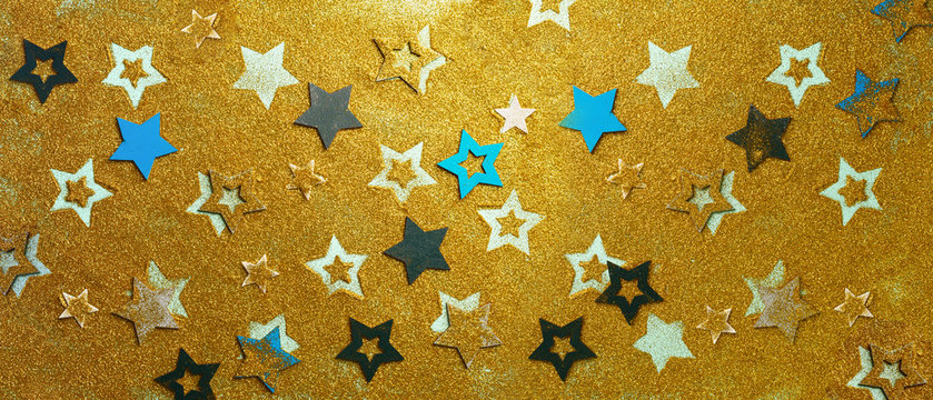 Christmas celebration. Abstract background for new year party. Patter of gold stars with lights, bokeh. Golden glitter stars on yellow shimmer texture. Banner