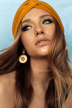 portrait of beautiful young woman with brown hair and freckles face