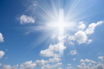 Christian shining cross in blue cloudy sky