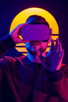 Man wearing virtual reality glasses headset. Vr world experience. Videogame in 80's synthwave and retrowave futuristic aesthetics.