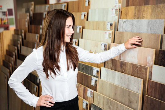 Beautiful young woman on position of manager or seller with dark hair looks different types and colors of floor coloring in a small store