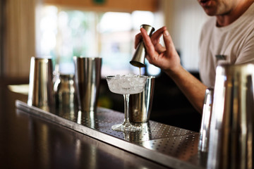 waiter pouring gin in a cocktail
