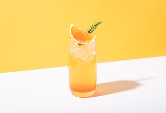 Cold and refreshing orange punch cocktail with orange slice on yellow background. summer drink.