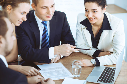 Group of business people and lawyers discussing contract papers