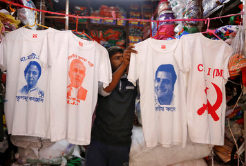A worker displays T-shirts with images of Mamata Banerjee, Narendra Modi, Rahul Gandhi and logo of Communist Party of India (Marxist), for sale inside a shop at a market ahead of India's general election, in Kolkata