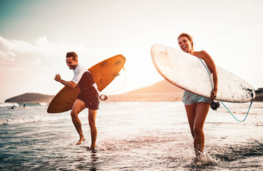Obraz Happy surfer couple running with surfboards along the sea shore - Sporty people having fun going to surf together at sunset - Extreme surfing sport and youth relationship lifestyle concept - fototapety do salonu