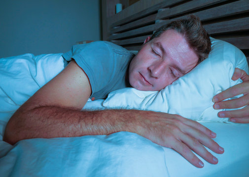 young attractive and handsome tired man on his 30s or 40s in bed sleeping peacefully and relaxed at apartment bedroom resting comfortable at night
