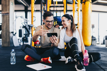 Male fitness gym instructor resting and sitting with young attractive woman on floor while making workout plan on his smart phone.