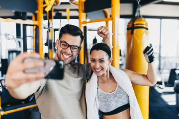 Young and attractive man and woman couple smiling and posing while making selfie photo in modern fitness gym.