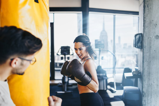Young attractive woman with instructor on kickboxing training. She hitting or punching in big yellow boxing bag.