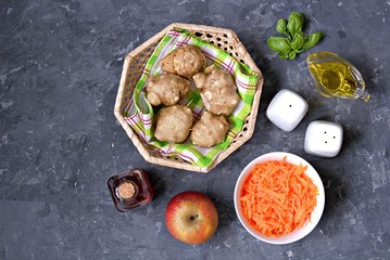 Ingredients for cooking vegetable salad: raw Jerusalem artichoke in wicker basket, raw grated carrots, apple, olive oil, red wine vinegar, fresh basil, salt, pepper. Top view. Copy space.
