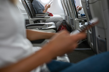 Passangers in abord a commercial flight using their cell phones during flight