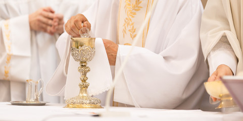 Priest' hands during a wedding ceremony/nuptial mass (shallow DOF; color toned image)