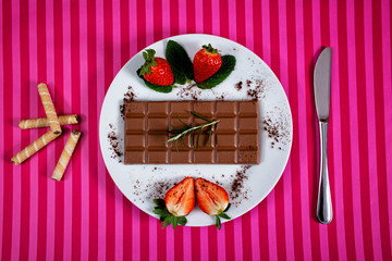 A bar of chocolate and strawberries on a plate with knife and waffles