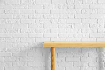 Table near white brick wall