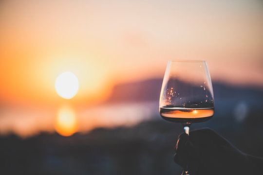 Man's hand holding glass of rose wine and with sea and beautiful sunset at background, close-up, horizontal composition. Summer evening relaxed mood concept