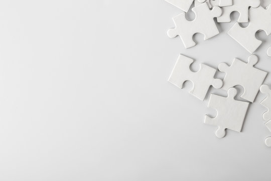 Heap of white puzzle pieces on light background