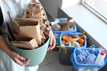 Woman holding trash bin with paper garbage indoors